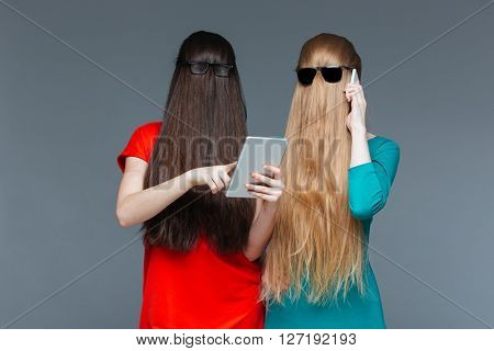Two amusing young women with faces covered by long hair using tablet and cell phone over grey background