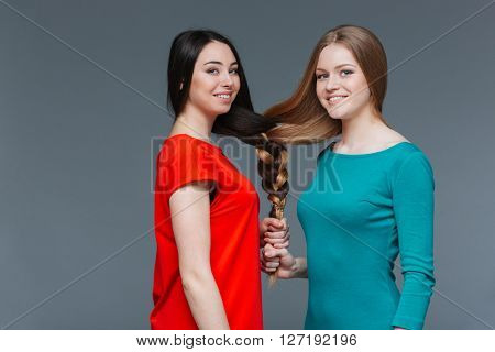 Portrait of two happy charming young women made one brair with their hair over grey background