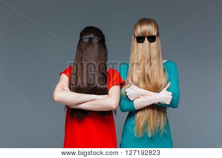 Two funny young women covered face with long hair and standing with arms crossed over grey background