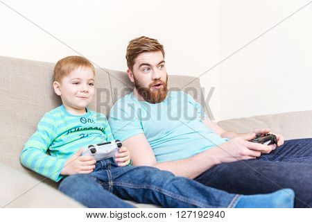 Amazed happy father playing computer games with his son on sofa at home