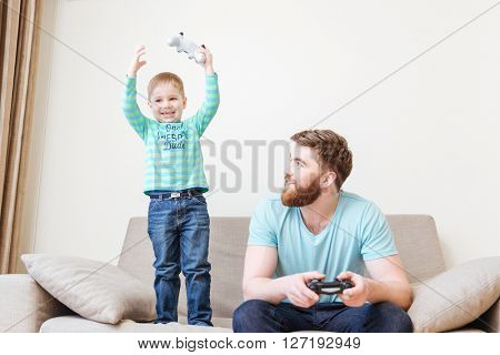 Happy cute little boy playing computer games with his dad and winning