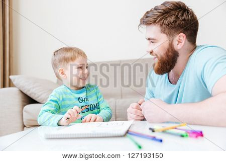 Cheerful little son and father drawing and having fun at home