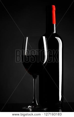 Wine glass and bottle of red wine on dark background