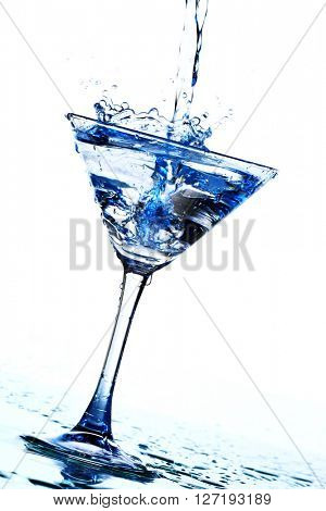 Splash of pouring cocktail into martini glass