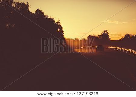 Dusty road with cars in the evening. Outdoors photo.