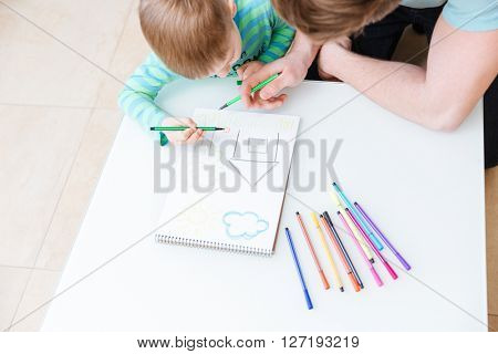 Top view of father and son drawing house together at home