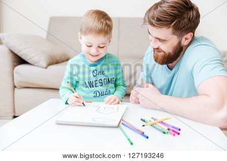 Smiling dad and little son drawing with colorful markers at home