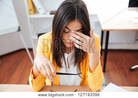 Tired businesswoman sitting at her workplace in office