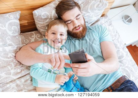 Top view of dad and son lying on bed and using cell phone together