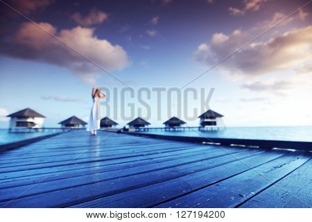 Woman walking on wooden bridge to hotels extended into the sea at maldives