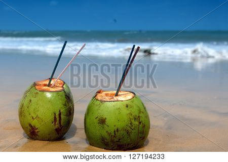 Two coconut cocktails on tropical beach