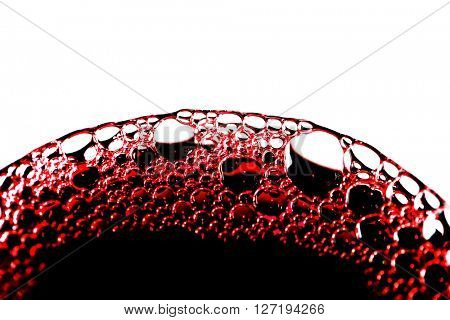 Closeup of red wine bubbles in glass isolated on white background
