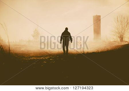 Silhouette of the walking person and tower. Evening photo.