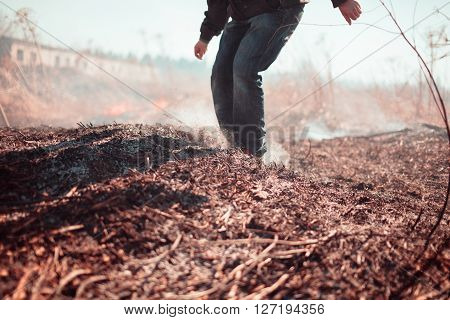 Legs of the person extinguish fire. Outdoors photo.