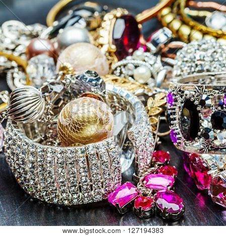 Many fashionable women's jewelry. Brilliant bangles on background