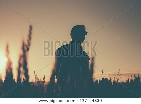 Silhouette of a man with glasses in the field on a belt. Evening photo.