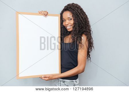 Smiling afro american woman showing blank board over gray background