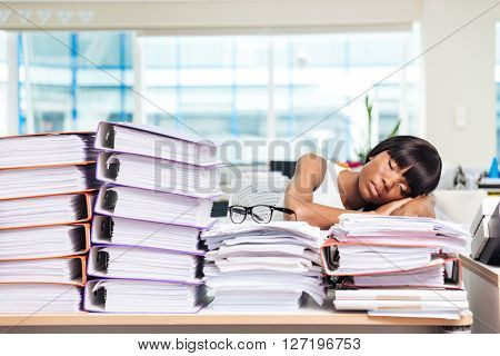 Afro american businesswoman sleeping on the papers in office