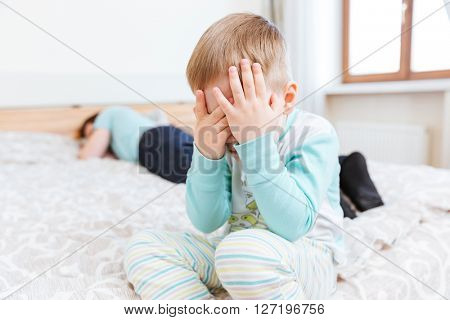Sad little boy sitting and crying on bed while his father is sleeping