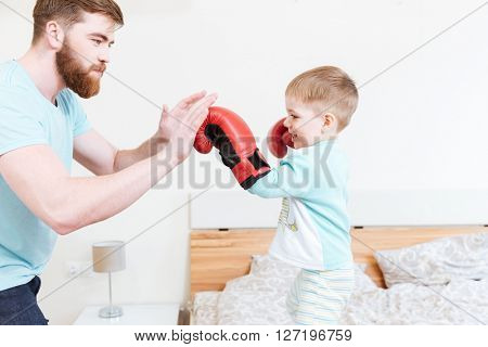 Cute little son in boxing gloves playing with his father at home