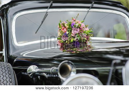 Elegant bridal bouquet of different flowers on the hood of a black retro car. Lacquered surface reflection. Windshield in the background. Headlight and retro car horn in front. Focus on a bouquet.