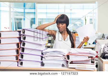 Shocked afro american businesswoman sitting at the table with many papers in office