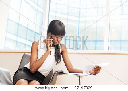 Beautiful afro american businesswoman talking on the phone and reading paper in office