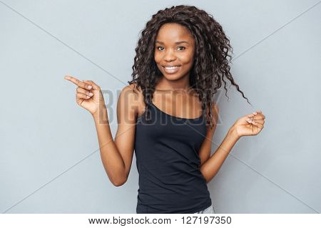 Smiling afro american woman pointing finger away over gray background