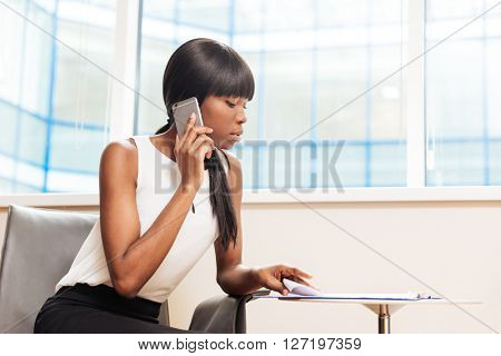 Afro american businesswoman talking on the phone and reading paper in office