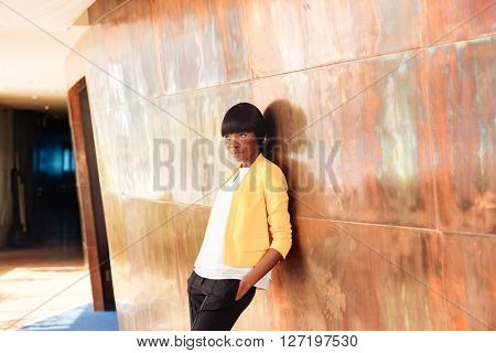 Beautiful afro american businesswoman leaning on the wall in office