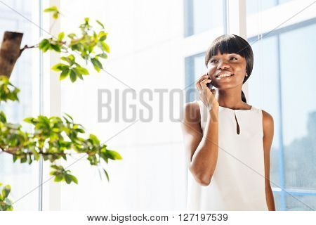 Happy afro american woman talking on the phone in office and looking away
