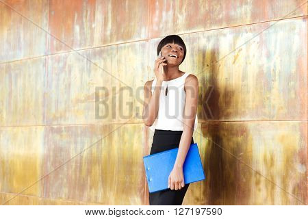 Smiling afro american woman talking on the phone in office