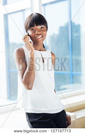 Happy afro american businesswoman talking on the phone in office and looking at camera