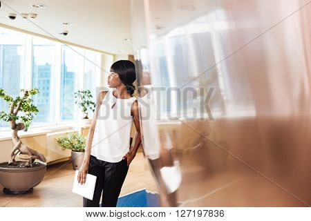 Pensive businesswoman leaning on the wall in office