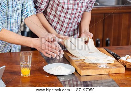 Hands of young couple standing and kneading dough on the kitchen