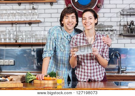 Happy young couple cooking and using tablet on the kitchen together