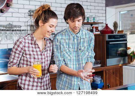 Beautiful young couple drinking orange juice and cooking using flour on the kitchen