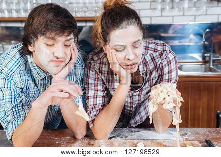 Sad bored young couple with flour on their faces kneading dough on the kitchen
