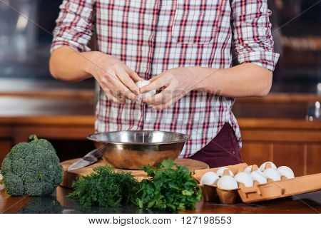 Hands of young woman breaking eggs and cooking on the kitchen
