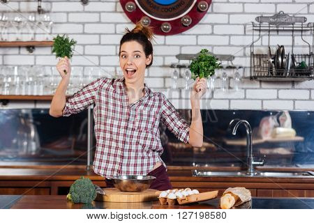 Cheerul pretty young woman holding dill and parsley on the kitchen