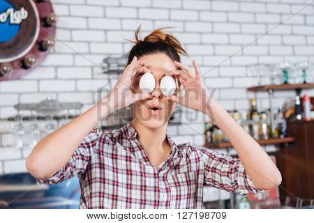 Funny young woman covered eyes with eggs and having fun on the kitchen