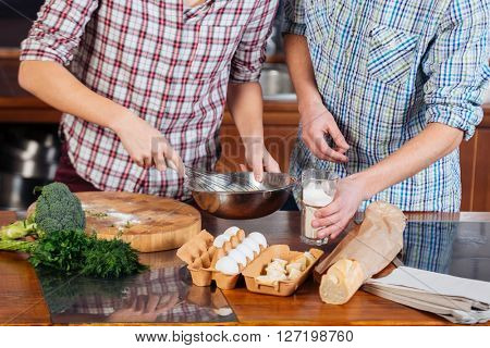 Closeup of hands of young couple beating eggs and cooking together on the kitchen