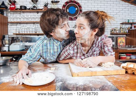 Amusing young couple with flour on faces making funny faces on the kitchen together