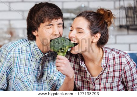 Happy young couple biting broccoli together in the kitchen