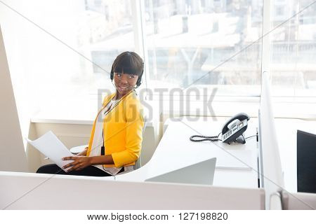 Happy afro american businesswoman working in office and looking away