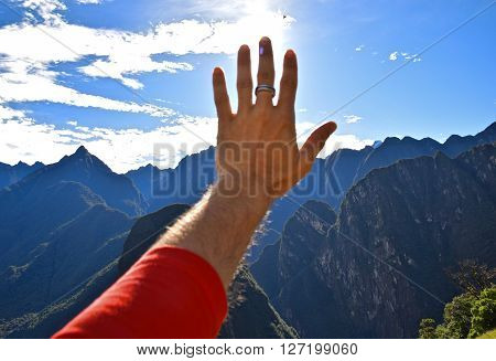 Fingertips obscuring sun form inside Machu Pichu. Peru - South America.