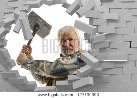 Determined man with hammer in hands and brick wall