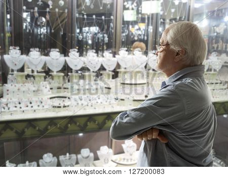 Senior man looking to jewellery showcase or shop window