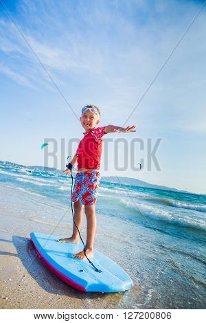 Young little boy learning to surf board