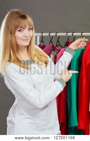 Pretty happy woman pointing at her clothing from wardrobe. Young undecided shopper girl bought new clothes. Shopping sale concept.
